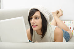 Young brunette student lying on the couch with a laptop Stock Images