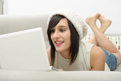 Young brunette student lying on the couch with a laptop Stock Photography