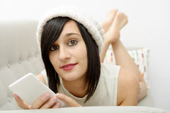 Young brunette student lying on the couch with phone Royalty Free Stock Images