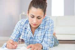 Young brunette student lying on the floor doing assignments Stock Photo