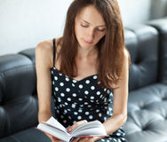 Young brunette student reading a book Stock Image