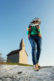 Young brunette in a stylish hat and an old romanesque church Arc. Young brunette posing in a stylish hat. Cowboy style. Old romanesque church Archangel Michael Royalty Free Stock Photo