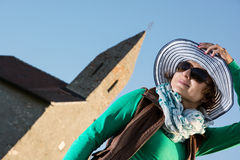Young brunette with stylish hat and old romanesque church. Young caucasian brunette with stylish hat and old romanesque church in sunset Royalty Free Stock Photos