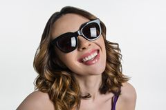 Young brunette in sunglasses looks at camera and smiles. stock image