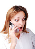 Young brunette with surprised expression on face. Speakin on cell phone Royalty Free Stock Photography