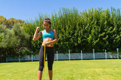 Young brunette sweating athlete in sportswear. Measuring her waistline after a workout at the park Royalty Free Stock Photo