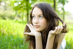 Young brunette teenager girl on meadow Royalty Free Stock Image