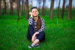 Young brunette tender beautiful woman with closed eyes sitting on grass relaxing. Resting in sunny weather in field on bright green background. Lifestyle Stock Image