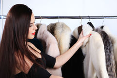Young brunette touched fur coat standing near hangers Stock Photography