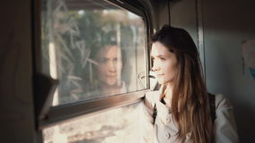 Young brunette traveling by train. Attractive girl looking at window to landscape outside, doing up the hair. Young brunette traveling by train. Attractive girl stock footage