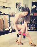 Young brunette trying sandals in footwear shop Stock Images