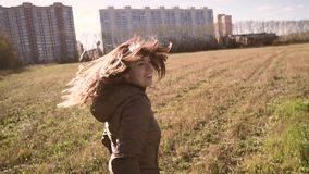 Young brunette turns around in front of a man and smiles at him. They walk in the Park. On the horizon can be seen at. Home. Slow motion. Video first person stock video footage