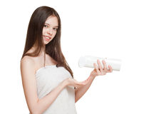 Young brunette using body lotion. Royalty Free Stock Image