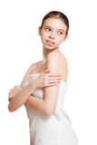 Young brunette using body lotion. Royalty Free Stock Photography