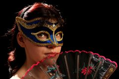 Young brunette with venetian mask and spanish fan. Isolated on black Stock Photo
