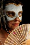 Young brunette with venetian mask and spanish fan Stock Images
