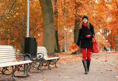A young brunette walking down the Autumn street Stock Photo