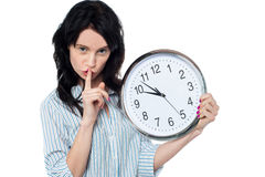 Young brunette with wall clock gesturing silence. Serious faced young woman with wall clock in hand gesturing silence Stock Photography
