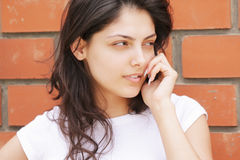 Young brunette at wall talking cellphone Royalty Free Stock Photography