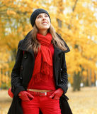 A young brunette in warm red Autumn clothes Stock Images
