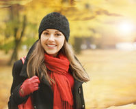 A young brunette in warm red autumn clothes Stock Photography