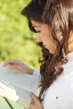 Young brunette in white reading book sideview Stock Image