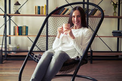 Young brunette with a wide smile sitting in a designer chair wit Stock Photos