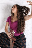 Young brunette woman with acoustic guitar in long skirt. Brick wall background Royalty Free Stock Image