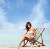 A young brunette woman adding suntan on the beach. A young and attractive brunette Caucasian woman in a white swimsuit adding spray on the beach. The image is Stock Photo
