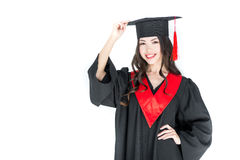 Young brunette woman adjusting mortarboard and smiling at camera Royalty Free Stock Image