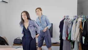 Young brunette woman is applying jeans jacket and consulting with her personal image-maker in home. Two woman are communicating stock footage