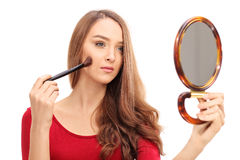 Young brunette woman applying make-up Royalty Free Stock Photo