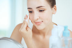A young brunette woman applying powder looking in the round mirr Royalty Free Stock Photo