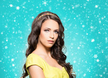 Young brunette woman in beautiful jewelry. Beautiful brunette with luxury golden necklace over cyan winter background. Christmas concept Royalty Free Stock Image
