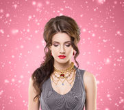Young brunette woman in beautiful jewelry. Beautiful brunette with luxury golden necklace over pink winter background. Christmas concept Royalty Free Stock Image
