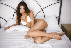 Young brunette woman on the bed Stock Photography