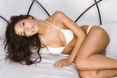 Young brunette woman on the bed Stock Images