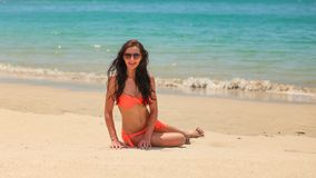 Young brunette woman in bikini and sunglasses, sitting on sand beach, calm azure sea background royalty free stock photo