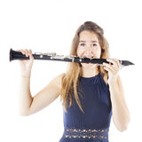 Young brunette woman bites clarinet in studio Royalty Free Stock Images