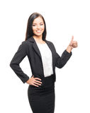A young brunette woman in black formal clothes on white. A young and confident brunette Caucasian woman posing in black formal clothes and holding thumbs up. The Royalty Free Stock Photo