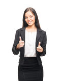 A young brunette woman in black formal clothes on white. A young and confident brunette Caucasian woman posing in black formal clothes and holding thumbs up. The Royalty Free Stock Photography