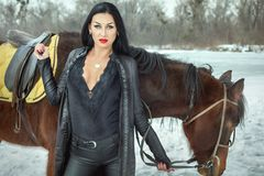 Brunette woman in black suit standing near horse royalty free stock photos