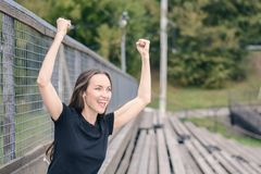 Young brunette woman in a black t-shirt one in the stadium rooting for your favorite team, enjoys raising his hands up and smiles. Emotional expression Royalty Free Stock Photos