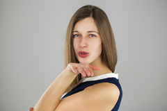 Young brunette woman blowing while sending an air kiss Stock Image