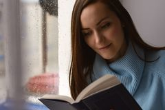Young brunette woman in blue woolen sweater, reading an interesting book on the windowsill in the room in the rain, cloudy and col. D weather Royalty Free Stock Images