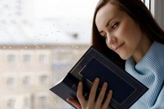 Young brunette woman in blue woolen sweater, reading an interesting book on the windowsill in the room in the rain, cloudy and col. D weather Royalty Free Stock Photography