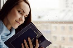 Young brunette woman in blue woolen sweater, reading an interesting book on the windowsill in the room in the rain, cloudy and col. D weather Royalty Free Stock Photo