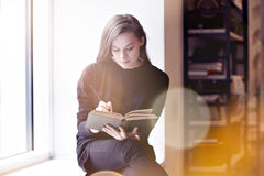 Young brunette woman with a book in a public library. royalty free stock images