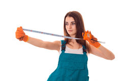 Young brunette woman builder in uniform makes renovations with measre tape in hands isolated on white background Royalty Free Stock Image