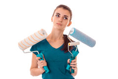 Young brunette woman builder in uniform makes renovations with paint roller in her hands posing and looking aside Stock Image